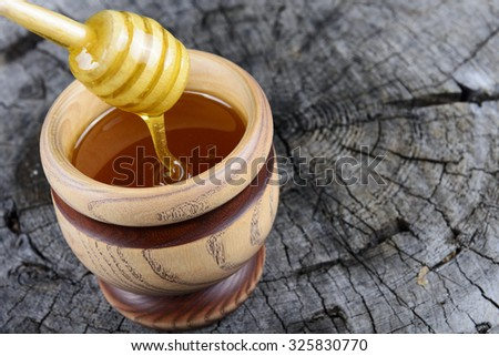 jar of honey and stick to honey on a wooden background - stock photo