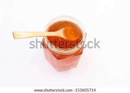 Jar of honey and wooden spoon isolated
