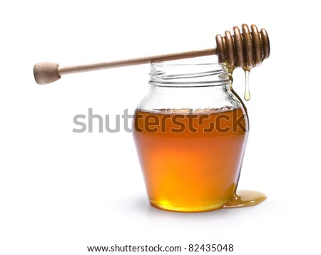 Jar of honey with a wooden drizzler on top. Isolated on white background.