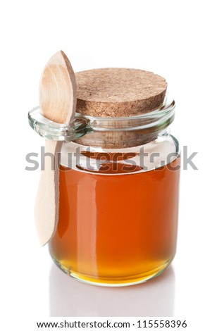 jar of honey with a wooden spoon on a white background