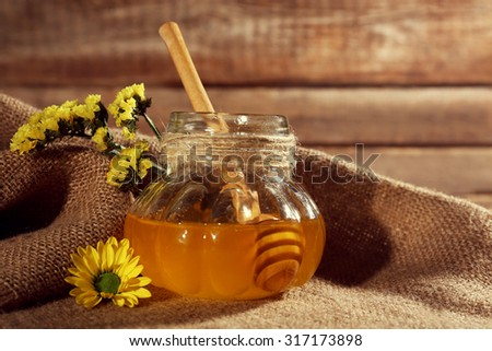 Jar of honey with flowers on sackcloth, close-up - stock photo