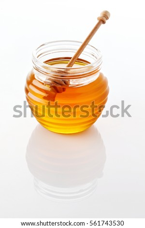 jar of honey with honeycomb on white