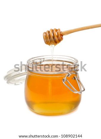 Jar of honey with wooden drizzler isolated on white - stock photo