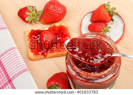 jar of jam with strawberries on wooden table
