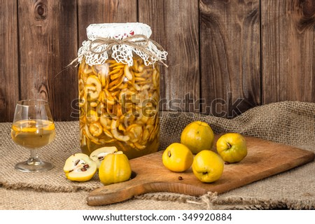 Jar of liquor and glass of drink with quince fruits on a jute background. - stock photo