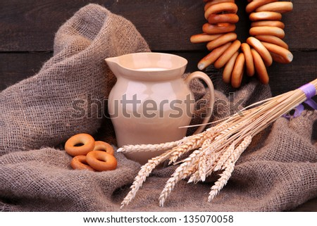 jar of milk, tasty bagels and spikelets on wooden background - stock photo