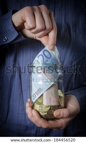 Jar of Money with hand picking up. - stock photo
