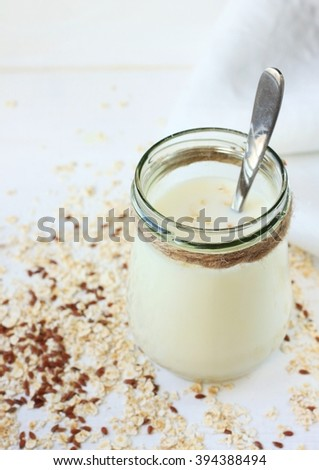 Jar of oat and flax seed milk. Rolled oats scattered on white table. - stock photo