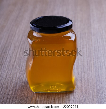 Jar of Orange Honey over a wooden background