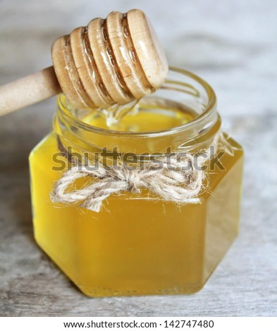 Jar of organic floral honey with a honey spoon