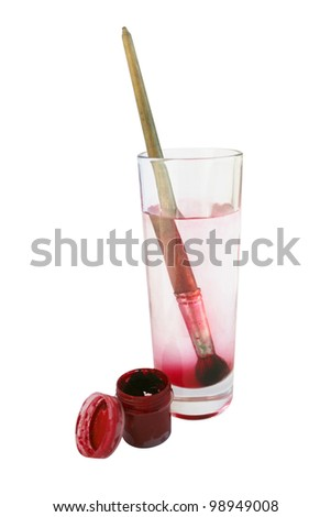 jar of paint red color and a brush in the glass with water - stock photo