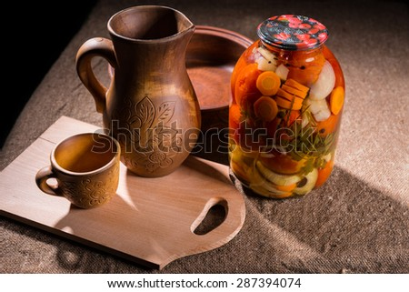 Jar of Pickled Vegetable Preserves on Rustic Burlap Covered Table Surface Next to Carved Wooden Handicrafts - Wood Pitcher, Cup, Bowl and Wooden Cutting Board - stock photo
