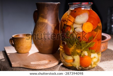 Jar of Pickled Vegetable Preserves on Table Surface Next to Carved Wooden Handicrafts - Wood Pitcher, Cup, Bowl and Wooden Cutting Board - stock photo