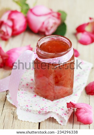 Jar of rose petal jam on a wooden table with flowers roses, selective focus - stock photo