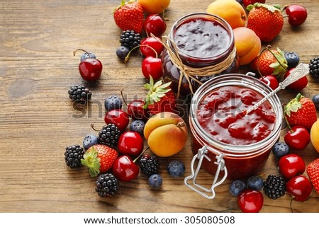 Jar of strawberry jams among summer and autumn fruits on a wooden table - stock photo