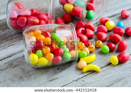 Jar scattered with candies on table - stock photo