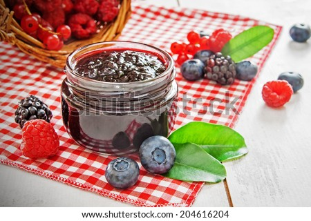 Jar with blueberry jam and scattered berries on wooden table - stock photo