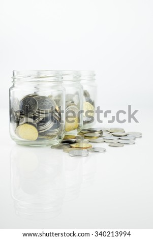Jar with coins. Selective focus over white background - stock photo