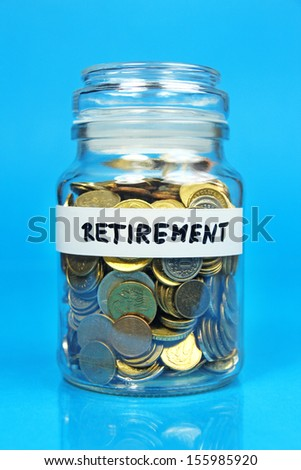 jar with coins with retirement label on blue background - stock photo