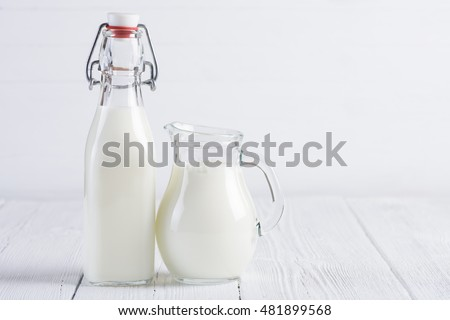 Jar with milk and vintage bottle of milk on white wooden table background still life