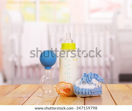 Jar with milk, booties and nipple close-up on a table in the children's room - stock photo
