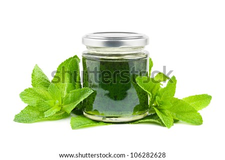 Jar with mint jelly and mint leaves on white - stock photo