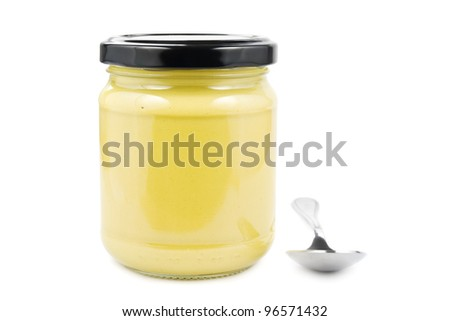 Jar with mustard and a spoon on white