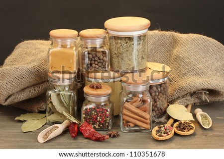 jars and spoons with spices on wooden table on black background