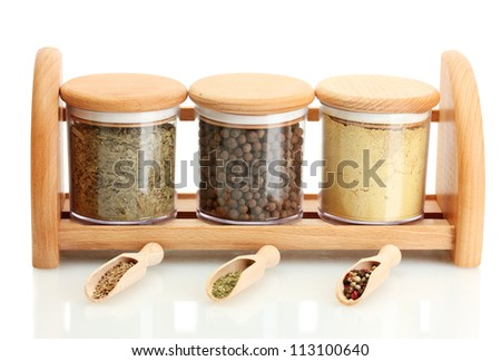 jars and wooden spoons with spices on wooden shelf isolated on white - stock photo