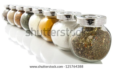 Jars filled with dried herbs on a white background - stock photo