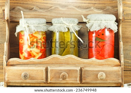 Jars full of vegetables on the shelf - stock photo