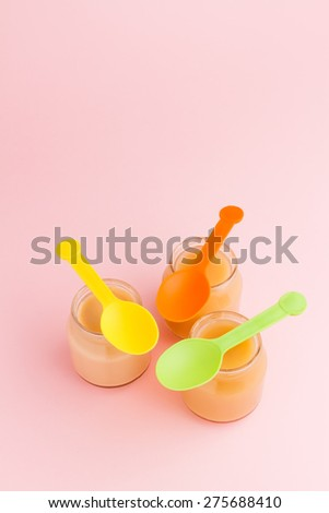 Jars of baby puree with colorful plastic spoons on pink background with copy space - stock photo