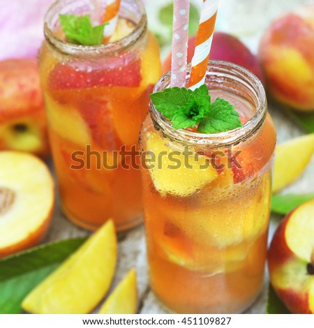 Jars of cold peach tea on fruit background, selective focus