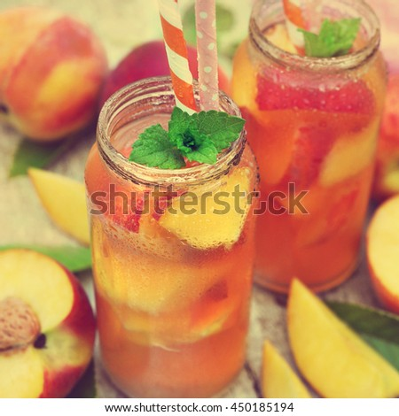 Jars of cold peach tea on fruit background, selective focus, toned