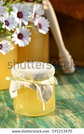 jars of delicious honey, flowers and honey dipper in apiary - stock photo