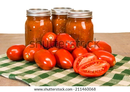 Jars of fresh tomato sauce with red paste tomatoes - stock photo
