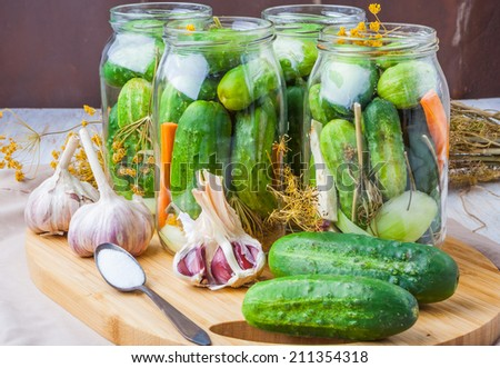 jars of homemade preserves with pickled cucumbers - stock photo