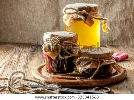 Jars of jam and honey on a wooden table. - stock photo