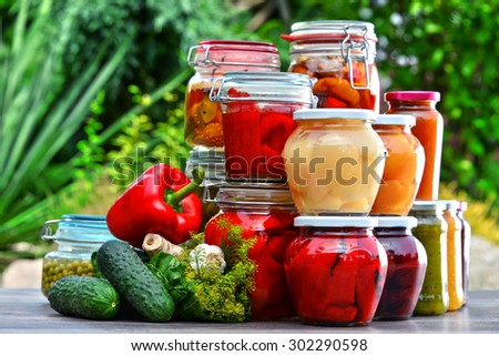 Jars of pickled vegetables and fruits in the garden. Marinated food. - stock photo