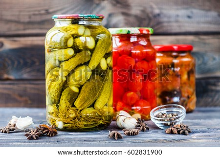 Jars of pickled vegetables: cucumbers, tomatoes, eggplants on rustic wooden background. Marinated and canned food.