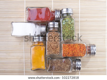Jars of spices on the wooden background - stock photo