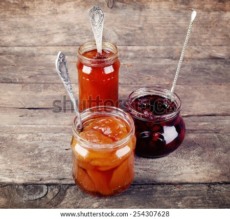 Jars of tasty jam on wooden background - stock photo