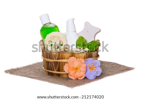 Jars with body care cosmetics in wooden basket and flowers on hessian cloth napkin, white background - stock photo