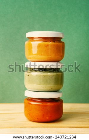 jars with colorful homemade jams or sauces on a wooden table over vintage background - stock photo