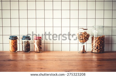 Jars with different grocery items on wooden kitchen table. Toned image - stock photo