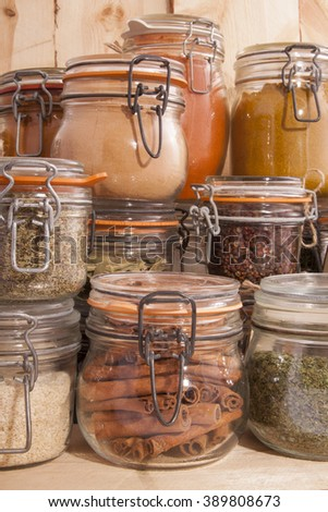 Jars with different kind of spices on wood