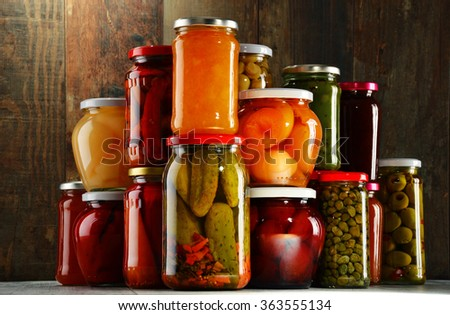 Jars with pickled vegetables, fruity compotes and jams in cellar. Preserved food - stock photo