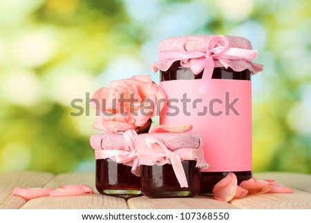 jars with rose jam and flower on wooden table on green background - stock photo