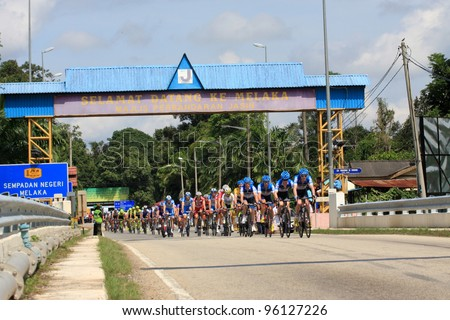 JASIN, MELAKA, MALAYSIA - FEBRUARY 26 : The largest group of cyclists from various teams cycle during Stage 3 of the Tour de Langkawi from Melaka to Parit Sulong on February 26, 2012 in Melaka, Malaysia. - stock photo