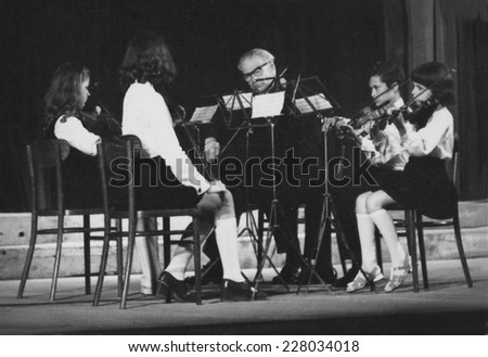 JASLO,POLAND - CIRCA 1975: vintage photo of young violinists with their teacher